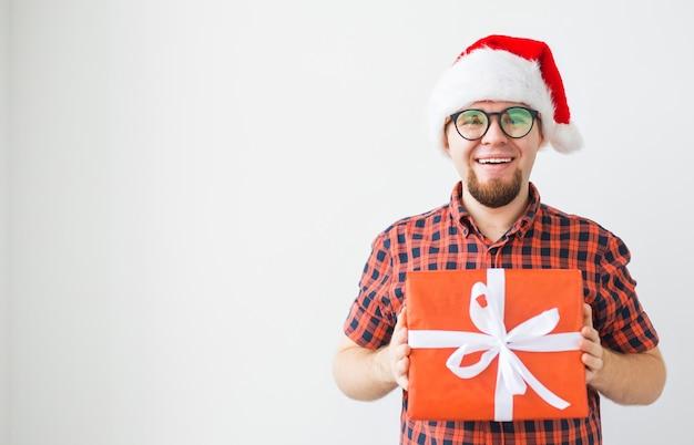 クリスマスと休日のコンセプト-コピースペースと白い背景の上の贈り物を保持しているサンタ帽子の面白い男