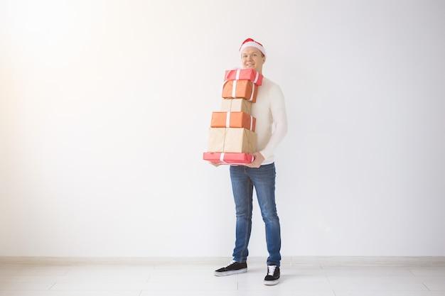白い背景の上にギフトボックスのスタックを保持しているサンタ帽子のクリスマスと休日のコンセプトの男