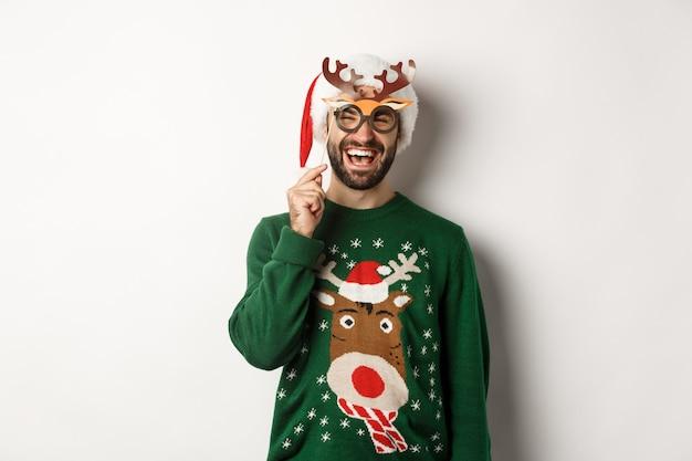 크리스마스와 휴일 개념입니다. 산타 모자를 쓴 수염 난 남자가 행복해 보이고, 새해 파티 마스크를 들고, 크리스마스를 축하하고, 흰색 배경 위에 서 있습니다.