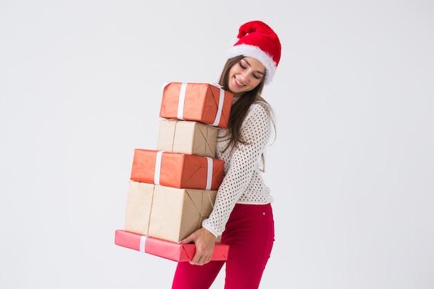 クリスマスと休日のコンセプト - 白い背景の上にギフト ボックスのスタックを保持しているサンタ帽子の女性