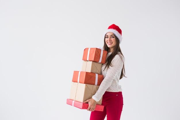 クリスマスと休日のコンセプト – コピースペースのある白い背景に多くの贈り物を持つサンタ帽子の女性
