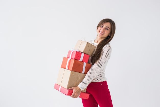 クリスマスと休日のコンセプト – コピースペースのある白い背景に多くの贈り物を持つ女性