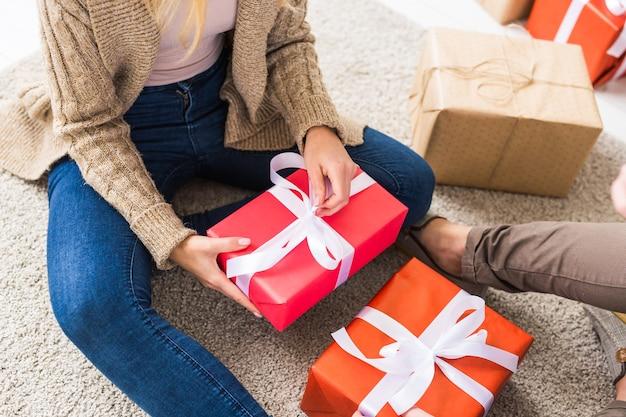 クリスマスと休日のコンセプト-家で贈り物を開くサンタの帽子をかぶっている若い幸せなカップル。