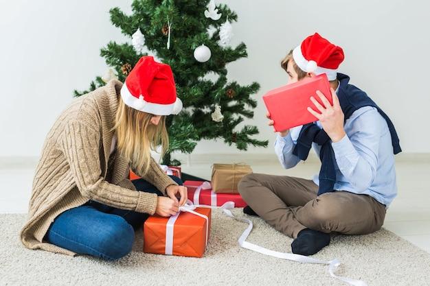 크리스마스와 휴일 개념 - 산타 모자를 쓰고 집에서 선물을 여는 젊은 행복한 커플.