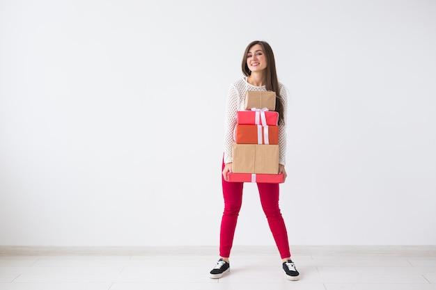 クリスマスと休日のコンセプト – コピースペースを持つ白い背景の上にギフトボックスのスタックを持つ若い女性