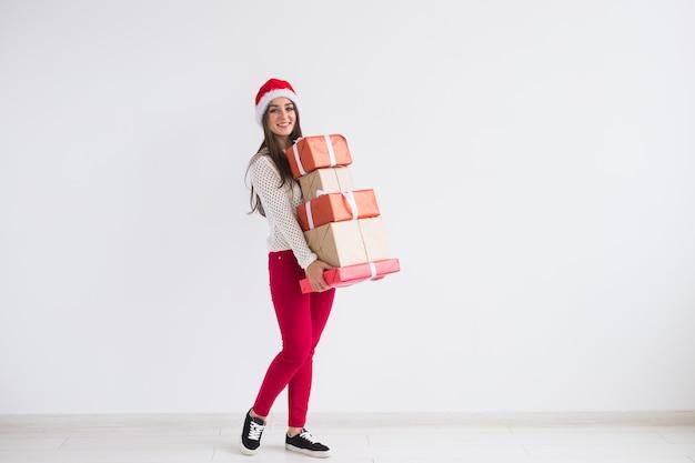 クリスマスと休日のコンセプト – コピースペースのある白い背景の上にギフトボックスのスタックを保持しているサンタ帽子の若い女性