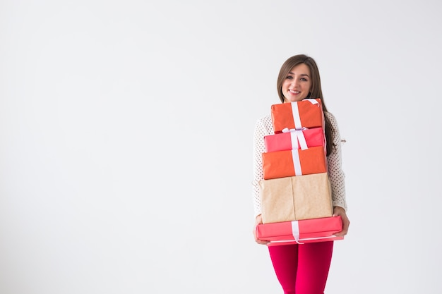 クリスマスと休日のコンセプト – コピースペースのある白い背景に多くの贈り物を持つ若い女性