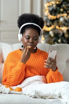 크리스마스와 새해에는 집에서 아프리카 여성이 소파에 앉아 겨울 방학 동안 일에서 휴식을 취합니다