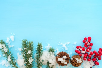 Christmas and New year background. Fir leaves, pine cones and red berry on blue wood table
