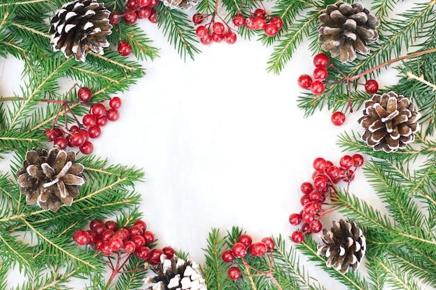クリスマスと新年の背景、緑のモミの枝と赤いベリーが額装され、明るい背景