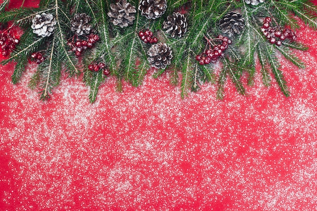 クリスマスと新年の背景、緑のモミの枝と雪と赤いベリー、赤い背景