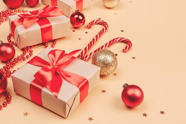 Рождество и новый год фон с копией пространства. празднично оформленные подарочные коробки, леденцы из тростника, новогодние шары на золотом баннере.