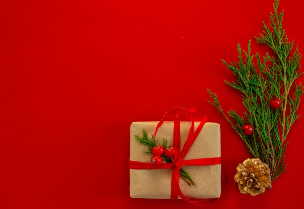 赤い背景のフラットレイコピースペースにクリスマスと年賀状の背景のトウヒの贈り物