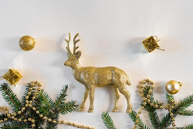 クリスマスと新年のカード。黄金の鹿とクリスマスツリースプルースの枝、金のビーズと黄金のおもちゃ
