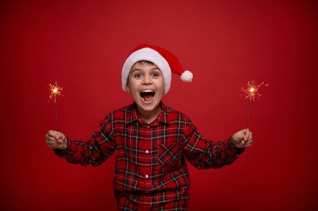 Концепция празднования рождества и нового года для рекламы. забавный удивительный красивый ребенок-мальчик в шляпе санты наслаждается вечеринкой, держащей бенгальские огни на красном фоне с копией пространства