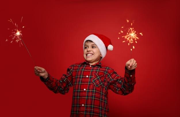 Концепция празднования рождества и нового года. забавный красивый ребенок мальчик в шляпе санты с бенгальскими огнями на красном фоне с копией пространства для рекламы