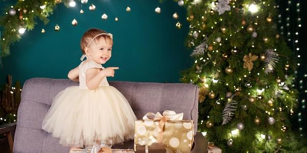Концепция празднования рождества и нового года. симпатичная маленькая девочка в белом платье, играя и радуясь рождественской елке и огням. зимние каникулы. копировать пространство