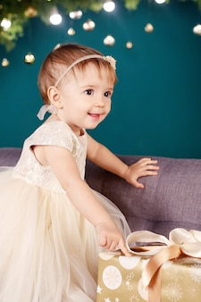 Концепция празднования рождества и нового года. симпатичная маленькая девочка в белом платье, играя и радуясь рождественской елке и огням. зимние каникулы.