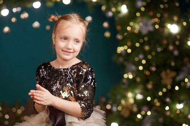 Концепция празднования рождества и нового года. симпатичная маленькая девочка играет и рада рождественской елке и огням. зимние каникулы.