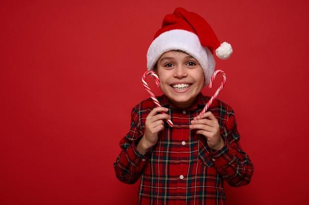 Концепция празднования рождества и нового года с пространством для рекламы. забавный удивительный красивый ребенок мальчик в шляпе санты радуется, глядя в камеру, держа в руках сладкие полосатые леденцы, сладкие леденцы на палочке.