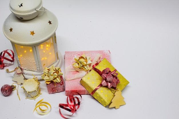 クリスマスと新年の構成。白い背景に装飾、ギフト、明るい弓が付いたお祝いの輝くランタン。