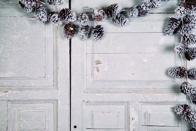 크리스마스와 새 해 구성 - 나무 흰색 문 배경에 소나무 콘. 가문비나무와 소나무 콘이 있는 오래된 질감 배경에는 크리스마스와 새해 복 많이 받으세요. 사이트 복사 공간