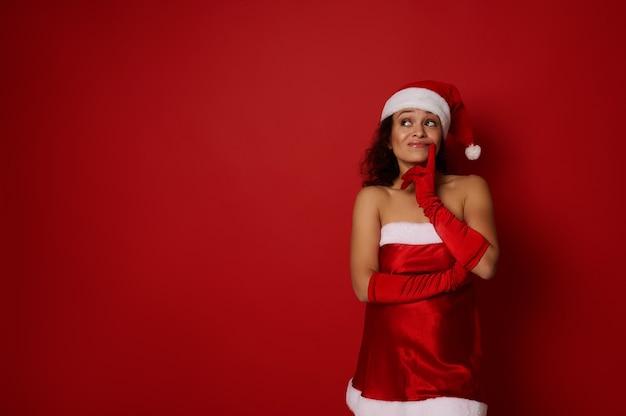 광고에 대 한 크리스마스와 새 해 개념입니다. 산타 카니발 의상을 입은 수심에 찬 신비한 아름다운 여성은 입술 근처에 손가락을 대고 빨간색 배경에 광고를 위한 카피 공간을 신중하게 올려다봅니다.