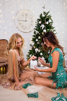 크리스마스와 새해 개념 - 장식된 크리스마스 트리가 있는 거실에 선물 상자가 있는 아름다운 드레스를 입은 두 여성