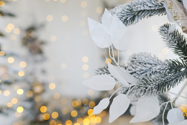 クリスマスと新年は白い葉とライトの背景でモミの木の枝を飾った