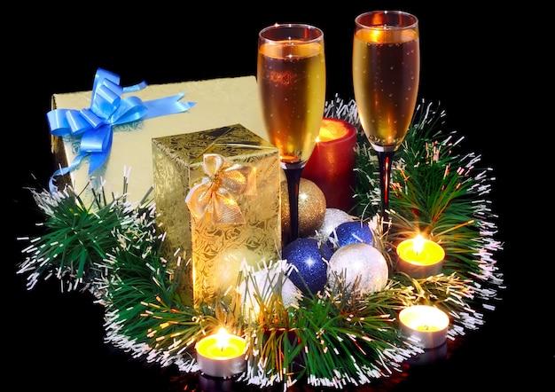 Рождественские и новогодние украшения-шары, мишура, свечи и бокалы с шампанским. на черном фоне.