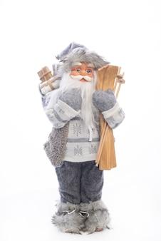 Рождественские и новогодние украшения. игрушечный санта-клаус с подарками в одной руке и лыжным снаряжением в другой, изолированные на белом.