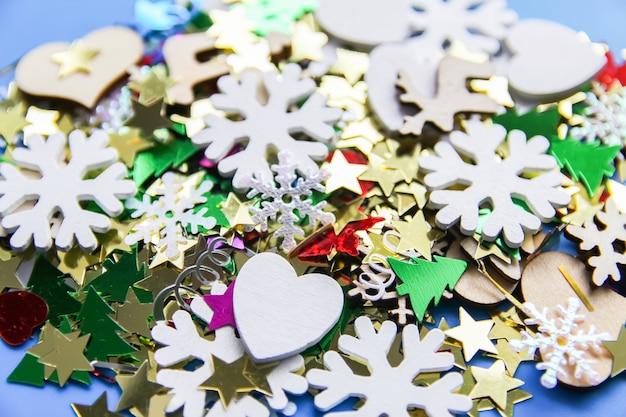 Рождество и новый год декоративный фон с небольшими деревянными снежинками. красочная мишура. праздничное конфетти.