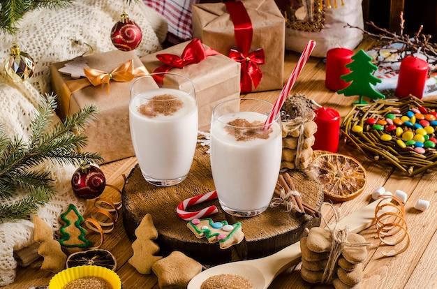Рождественский и новогодний напиток гоголь-моголь в стеклянных чашках на деревянной подставке на столе с подарками, рождественским печеньем, свечами, сладостями и ветками елки.
