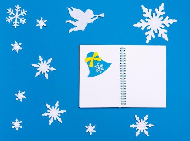 Рождественская и новогодняя плоская композиция с белым пустым блокнотом, синим колокольчиком, белым ангелом, играющим на трубе, и рождественскими снежинками на синем фоне