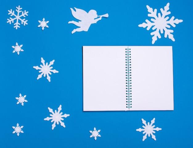 Рождественская и новогодняя плоская композиция с белым пустым блокнотом, белым ангелом, играющим на трубе, и рождественскими снежинками на синем фоне