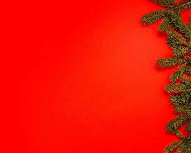 Рождественская и новогодняя рамка из еловых веток на красной плоской деревянной раме с видом сверху