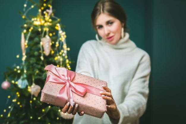 飾られた木と女性の手にリボンとクリスマスと新年のギフトボックス