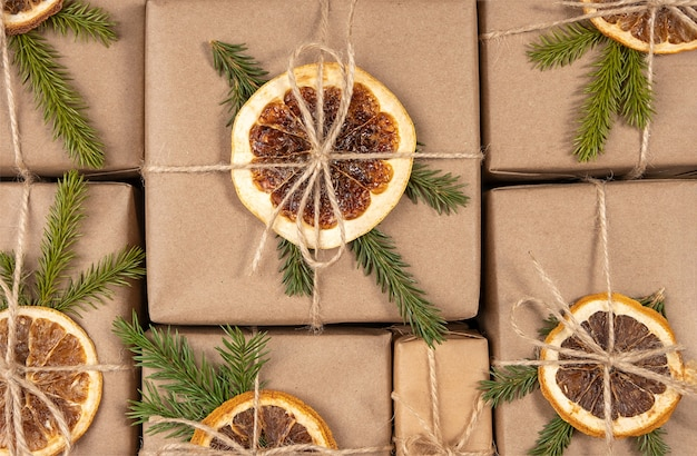 크리스마스와 새해 선물을 닫습니다. 말린 오렌지, 가문비나무 가지 및 꼬기로 장식된 공예 종이 상자. 컨셉 제로 웨이스트, 친환경 메리 크리스마스.