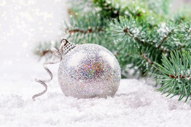 Рождественская и новогодняя открытка с серебряной блестящей безделушкой и веткой