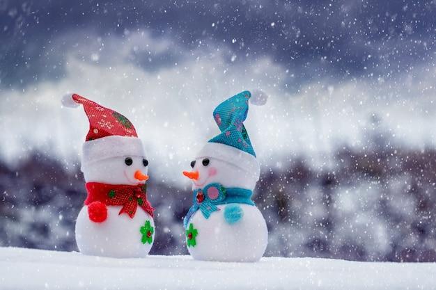 눈보라 동안 거리에 두 눈사람과 함께 크리스마스와 새해 인사말 카드