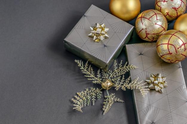 クリスマスと新年の手作りのラッピングギフトボックス、金色のリボン、ボール、黒のつまらないもの。