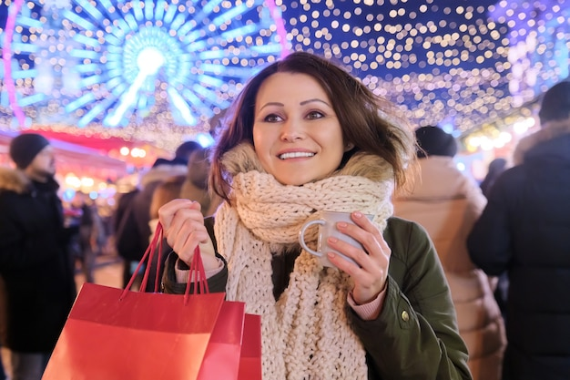 クリスマスと年末年始、クリスマスマーケットで買い物袋とホットドリンクのカップを持つ幸せな成熟した美しい女性