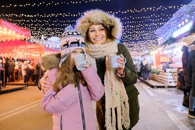 Рождественские и новогодние праздники, счастливая мама и дочка гуляют вместе, пьют горячий чай из кружки на рождественской ярмарке