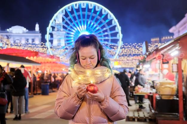 크리스마스와 연말 연시, 행복한 십대 소녀가 크리스마스 시장에서 빨간색 크리스마스 공 텍스트 2021에 씁니다.