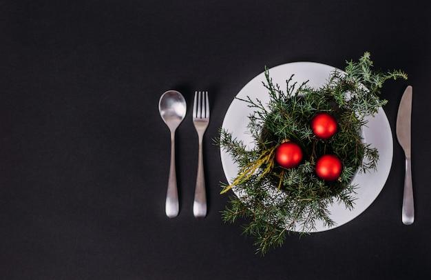 レストランとカフェでのクリスマスと新年。プレートには、クリスマスツリーの枝とクリスマスボールがあります。 copyspaceとフラットは黒の上に横たわっていました。