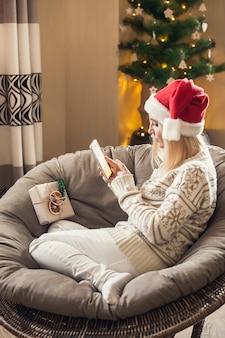크리스마스와 새해 온라인. 산타 모자를 쓰고 스마트폰을 사용하는 여자.