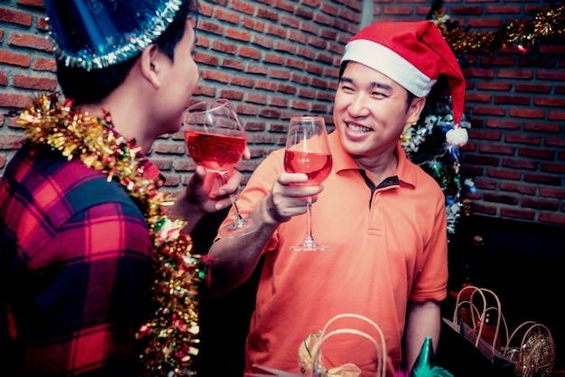 Рождественский и новогодний праздник с друзьями. гей-пара пьет красное вино в праздничную ночь.