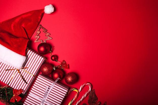 クリスマスと新年の赤い背景装飾ギフトボックス、サンタ帽子、おもちゃ