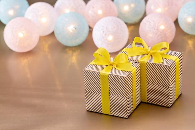 크리스마스와 새해 선물은 반짝이는 종이에 싸여 있고 배경에는 조명이 켜진 등불이 있습니다. 행복 한 겨울 휴가 개념, 스튜디오 촬영.