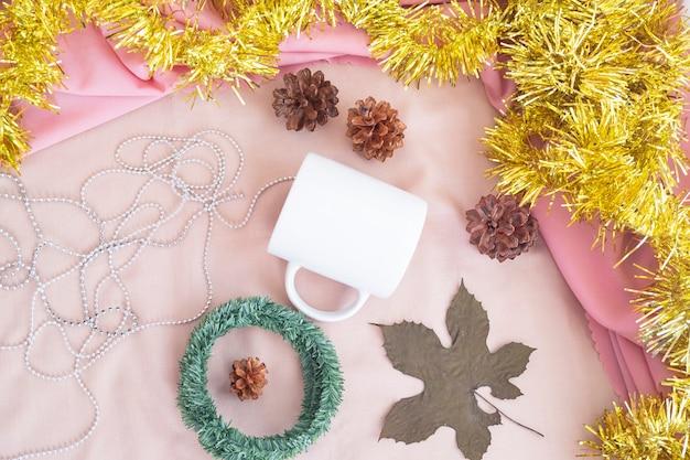 クリスマスと新年のミニマリストのコンセプト。製品マグをフィーチャーした構成。クリスマスと新年の装飾が施された上からの写真のマグカップ